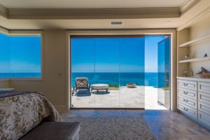 Looking at bedroom with stone flooring and shelving with enclosed frameless glass doors with one frame opened to the patio with an unobstructed view of the patio and ocean.