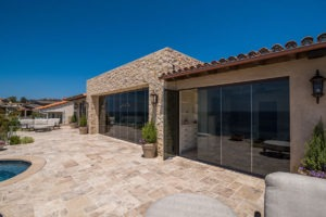 Looking at house with frameless glass doors enclosed from backyard with stone floor and pool.