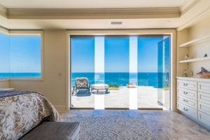 Looking at bedroom with stone flooring and shelving with staggered frameless glass doors with unobstructed view of the patio and ocean.