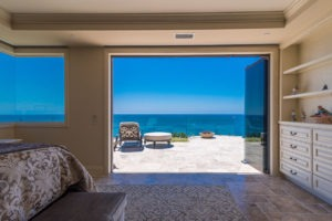Looking at bedroom with stone flooring and shelving with stacked frameless glass doors stacked to the right of the door frame with view of the patio and ocean.