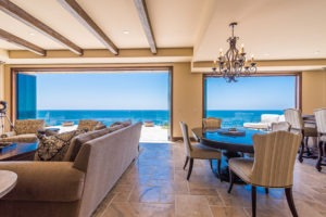 Open concept dining room and living room with stone floor and frameless glass doors stacked on sides of door frame with views of the ocean and patio.
