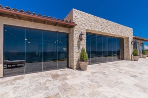 Looking at home from backyard with stone flooring and sliding glass doors enclosed.