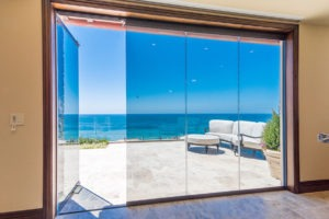 Looking at frameless sliding glass doors enclosed with one frame swung open allowing for unobstructed views of patio with stone floor, patio furniture and the ocean.