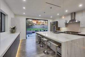 Kitchen with view of backyard with stacked frameless sliding glass doors.