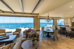 Looking at open concept living, kitchen and dining room with stone floor and frameless sliding glass doors enclosed allowing for unobstructed views of the ocean.