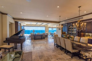 Looking at open concept living and dining room with stone floor and frameless sliding glass doors enclosed allowing for unobstructed views of the ocean.