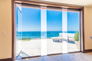 Looking at stone patio with patio furniture in corner with frameless sliding glass doors staggered in middle of door frame with one frame swung open allowing for unobstructed views of the ocean and patio.