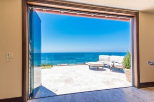 Looking at stone patio with patio furniture in corner with frameless sliding glass doors stacked on the right side of the door frame allowing for unobstructed views of the ocean and patio.
