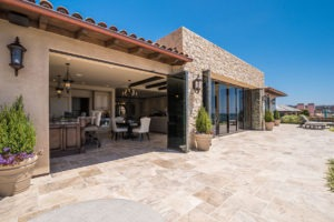 Looking from stone floor patio into open concept living, kitchen and dining room with two sections of the frameless sliding glass doors, one side stacked on the side of the door frame, the other staggered with two panels swung open..