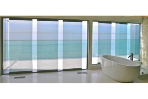 Bath tub with staggered frameless glass sliding doors and windows.