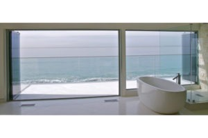 Bath tub with stacked frameless sliding glass doors and windows.