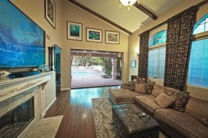 Frameless sliding glass doors connecting living area with tv and fire place with outdoor patio and swimming pool.