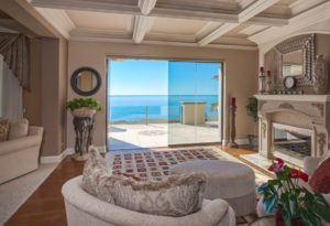 Living room with view of ocean and half enclosed frameless sliding glass doors.