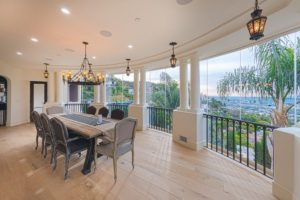 Enclosed frameless sliding glass door dining room patio with natural light and view of hill.