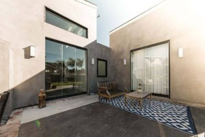 Outdoor patio in between two buildings featuring closed sliding glass doors.