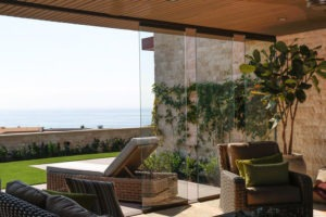 Partially open sliding glass doors connecting indoor patio with yard overlooking the ocean.