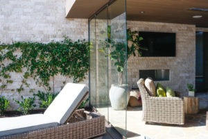 Partially open sliding glass doors connecting yard to indoor patio with tv and chairs.