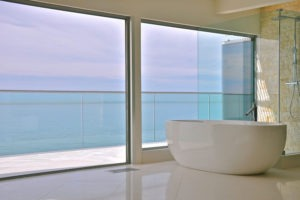 Intimate bath tub with stacked frameless sliding glass doors and windows.