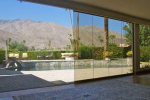 Living room with view of pool from half enclosed, half stacked frameless sliding glass doors.