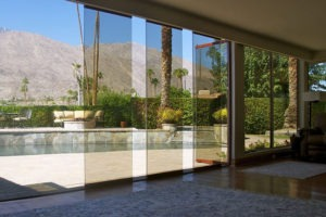 Living room with view of pool from staggered frameless sliding glass doors.