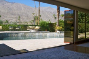 Living room with view of pool from stacked frameless sliding glass doors.