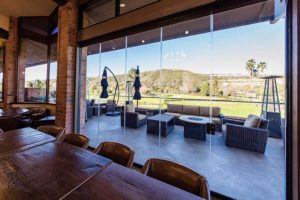 Country club with wood tables and leather chairs overlooking the yard through closed frameless sliding glass doors.