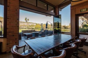 Country club with wood tables and leather chairs overlooking the patio and the yard through stacked frameless sliding glass doors.