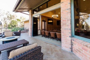 Outdoor patio looking into country club with stacked frameless sliding glass doors.