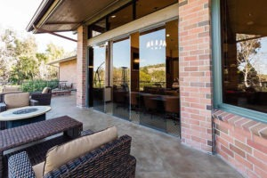 Outdoor patio looking into country club with partially open frameless sliding glass doors.
