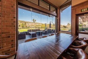Country club with wood tables and leather chairs overlooking the patio and the yard through frameless sliding glass doors.