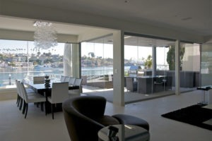 Inside living room of a home looking at the bay view through frameless glass windows.