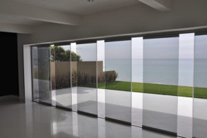 Empty room with partially open frameless sliding glass doors overlooking the ocean.