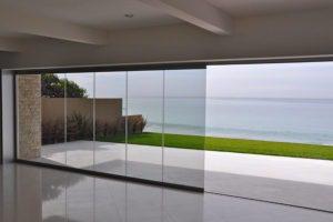 Empty room with half open frameless sliding glass doors overlooking the ocean.