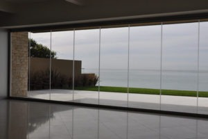 Empty room with fully closed frameless sliding glass doors overlooking the ocean.