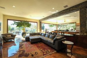 Open concept living room with dark brown sectional sofa and closed frameless sliding glass doors showing the outdoor patio.