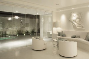Intimate living room with enclosed frameless sliding glass doors.