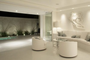 Intimate living room with stacked frameless glass doors.