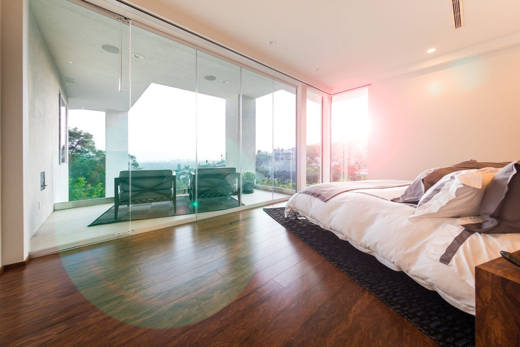 bedroom with frameless glass doors and view of city.