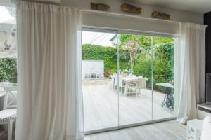 Enclosed frameless sliding glass doors with unobstructed views of backyard with fountain and table.
