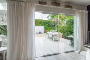 Staggered frameless sliding glass doors with an unobstructed view of the backyard with a fountain and table.