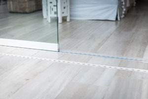 Looking at frameless sliding glass door track that keeps it secured in place.