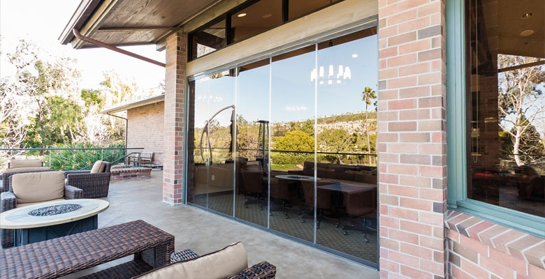 Outdoor resport patio with framless glass doors.