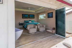 Looking into bedroom with wood flooring with frameless sliding glass doors stacked to the right of the doorframe from patio.