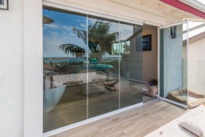 Looking from wooden floor patio at enclosed frameless sliding glass doors with one door frame swung open to the bedroom.