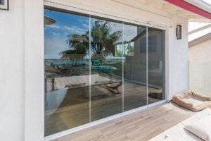 Looking from wooden floor patio at enclosed frameless sliding glass doors to the bedroom.