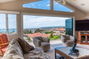 From living room looking out into bay with frameless sliding glass doors stack to one side.