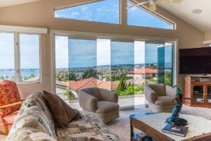 Looking from the living room to the patio with frameless sliding glass doors staggered with one door frame swung open in doorframe of the patio allowing for unobstructed views of the bay.