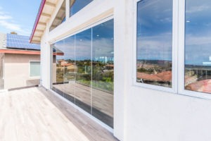 From wood floor patio looking at enclosed frameless sliding glass doors.