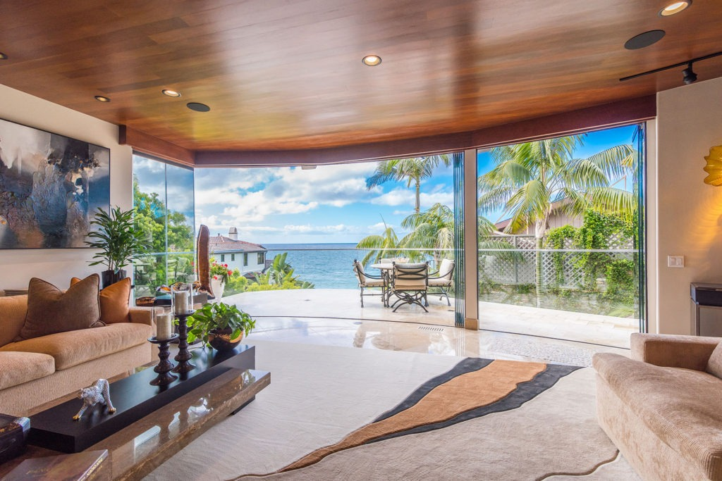 Opened frameless sliding glass doors with view of ocean.