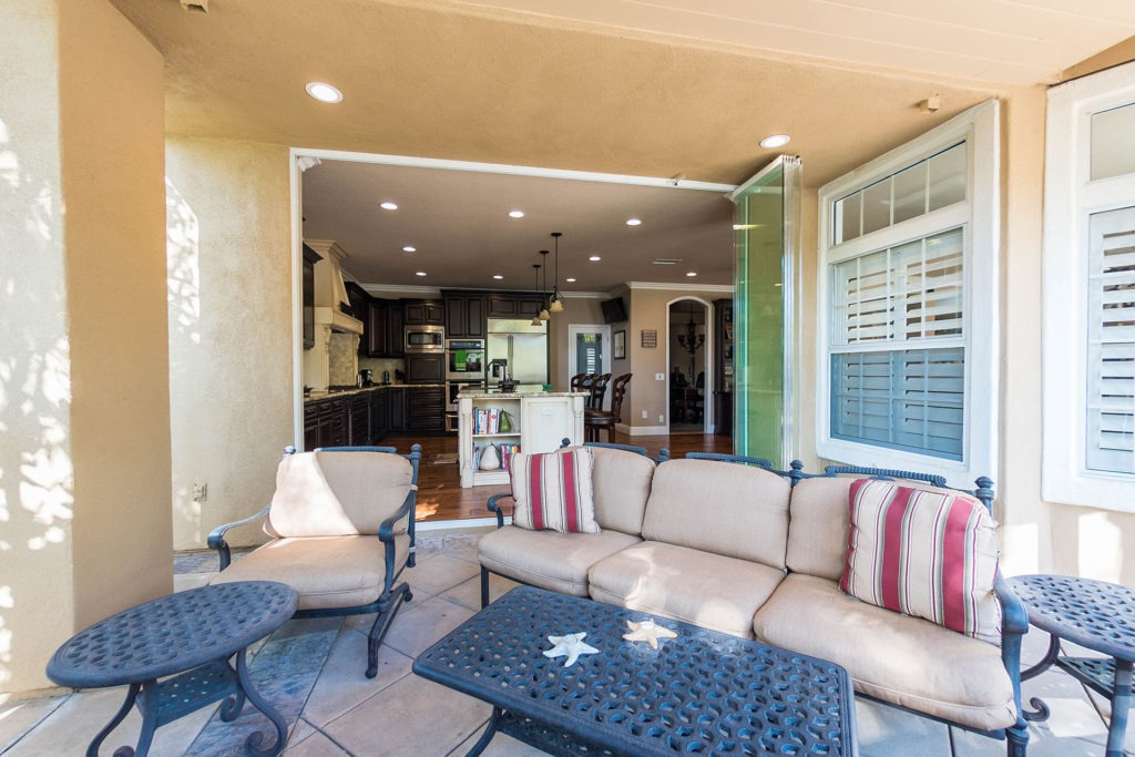 Patio with living room and stacked frameless sliding glass doors.